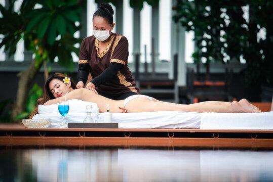 Asian beauty girls enjoy a massage by the resort's pool. Beauty treatment concept.
