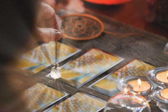 Hand with pendulum over tarot cards