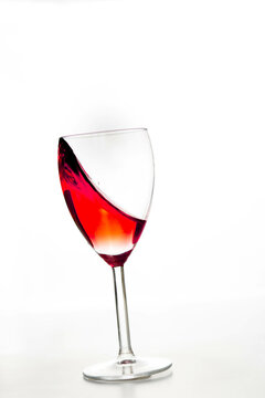 Glass of red wine drops on white background close up