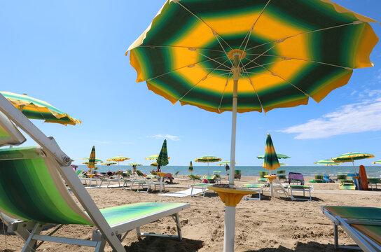 Deckchair on the beach under the umbrella during a hot summer day