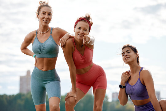 Happy women in fitness clothes relaxing and having fun in the park by the river. Fitness, sport, friendship and healthy lifestyle concept . Group of happy people exercising