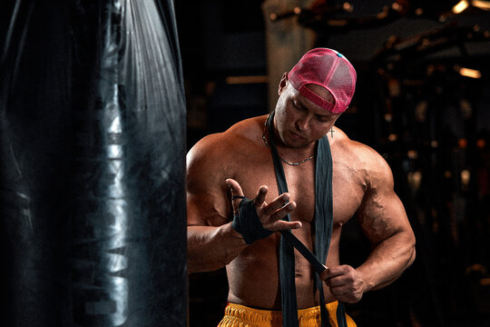 Strong athletic fitness men pumping up arm muscles workout barbell curl. Fitness concept background - muscular bodybuilder men doing bodybuilding biceps exercises in gym, naked torso