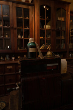 Scent bottles in old pharmacy. Wooden antique old pharmacy furniture for medical drug storage