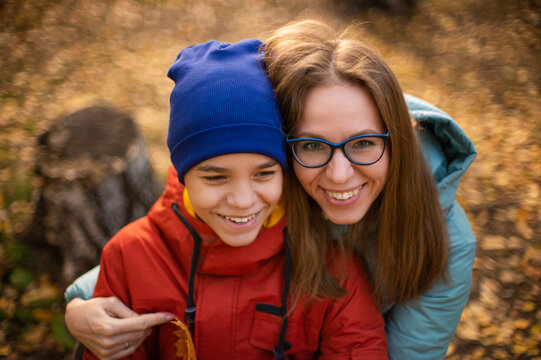 Autumn portrait of happy beautiful woman with her son on fall nature background