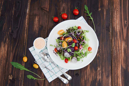 delicious bowl of fresh salad with dressing on a wooden table, tomato rocket, top view