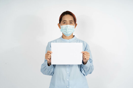 A  Middle age asian woman in a blue shirt wearing a medical face mask, holding an empty card. blank space template to be written. Encourage health care from Covid 19 corona virus, on white background