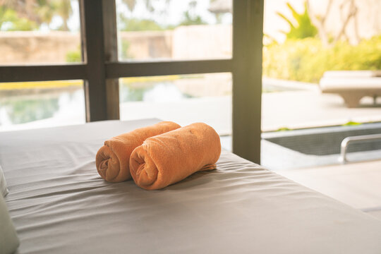 Folded orange towels decoration in stylish room interior, villa resort vacation