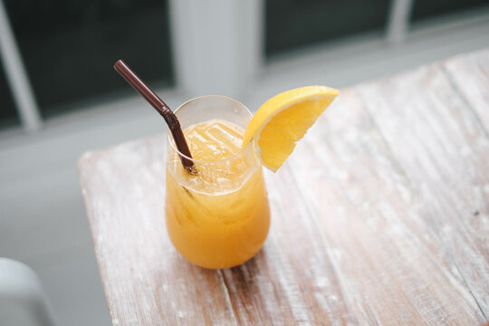 Glass of fresh orange juice and  straw on the wooden table in cafe house.