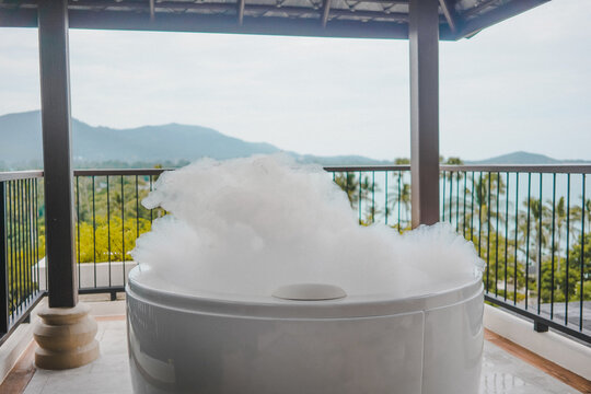 Bathtub with soap bubbles, Luxury jacuzzi suite for relaxation on balcony with landscape of sea view, Samui, Thailand