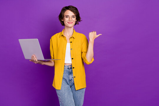 Portrait of attractive trendy cheery girl holding laptop showing copy space isolated over bright violet purple color background