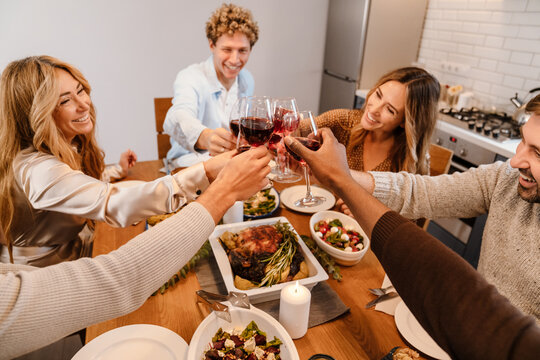 Multiracial happy friends drinking wine during thanksgiving dinner
