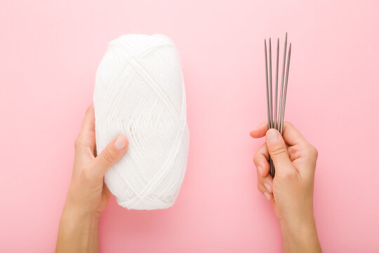 Young adult woman hands holding white wool clew and metal needles on light pink table background. Pastel color. Closeup. Point of view shot. Knitting clothes or other things. Top down view.