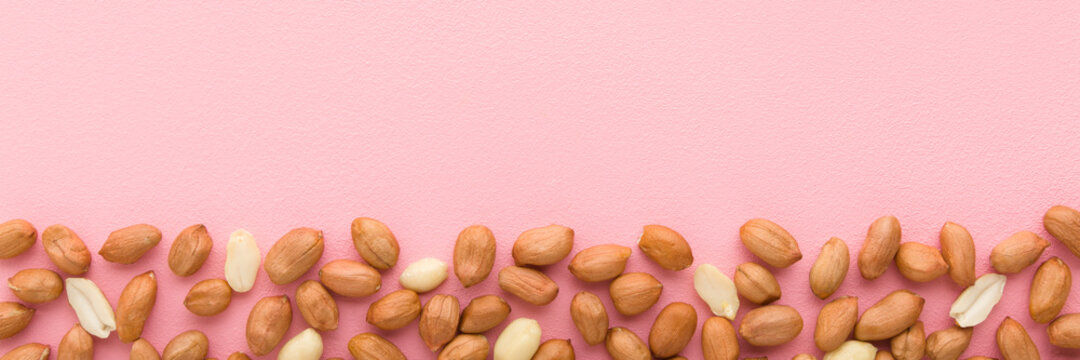 Brown almond nuts on light pink table background. Pastel color. Closeup. Food wide banner. Empty place for text. Top down view.
