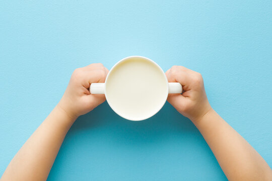 Toddler hands holding cup of white fresh milk on light blue table background. Pastel color. Closeup. Point of view shot. Daily healthy drink. Top down view.