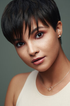 Portrait of beautiful young woman with short hair and and nice makeup on her face isolated on studio background