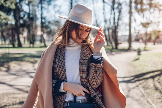 Portrait of fashionable woman wearing stylish clothes and accessories in park. Spring female outfit.