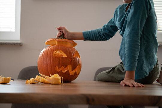 Child finishing a homemade halloween pumpkin