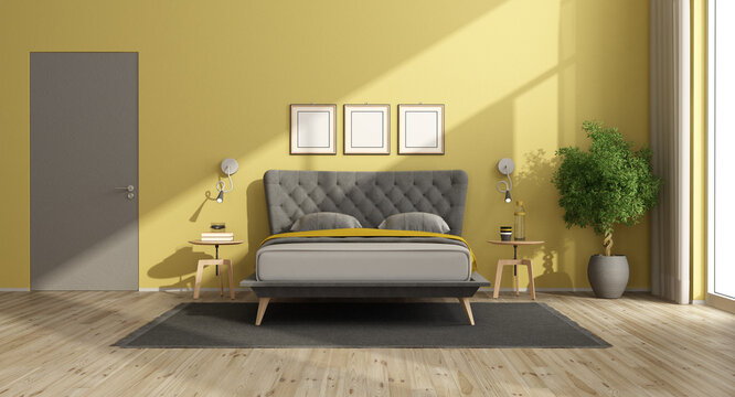 Modern bedroom with yellow walls and gray bed
