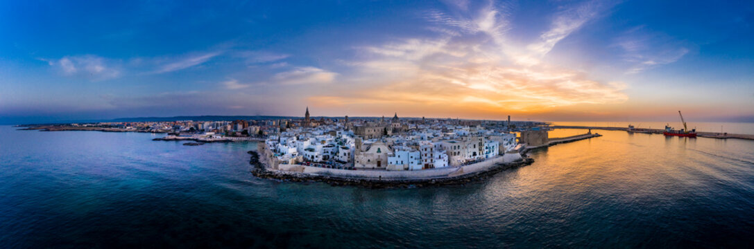 Italy, Apulia, Monopoli, Aerial view of sea and old town at sunset