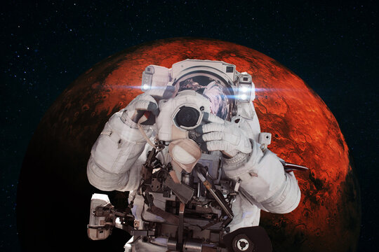Astronaut photographer with a camera taking pictures against the background of the red planet Mars. Space Mission Concept