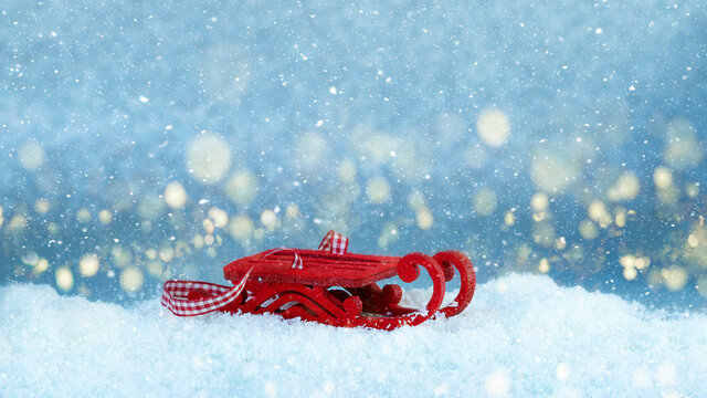 Red sleigh on snow. Festive image with golden bokeh