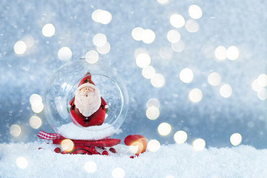 Santa Claus figure in glass ball on snowy background with golden bokeh