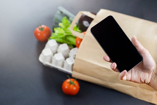 Smartphone in hand against paper bag full of food. Food delivery concept
