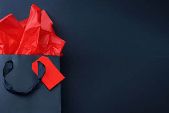 Close up of black gift bag with red tissue paper on black background