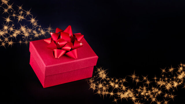 Red present box with red bow on black background with sparkles