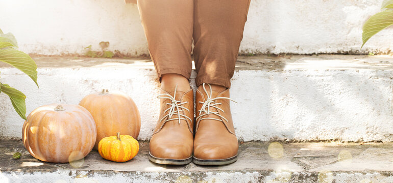 Woman is sitting on the stairs with three pumpkins close to her