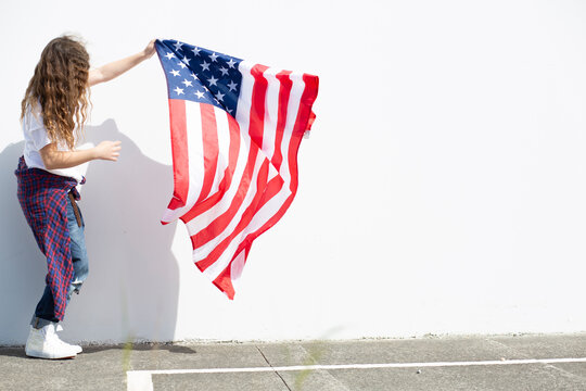 Girl holding American flag at white wall