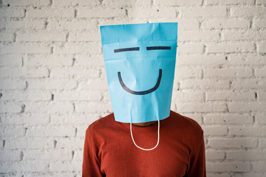 Mid adult man wearing blue paper bag on face against white brick wall