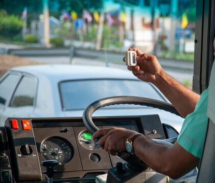 Driver using a mobile camera while driving a bus.