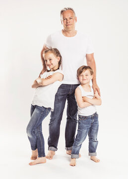 Portrait of father with two children standing in front of white background