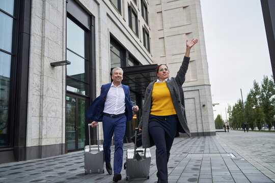 Business colleagues running with wheeled luggage on footpath while waving in city