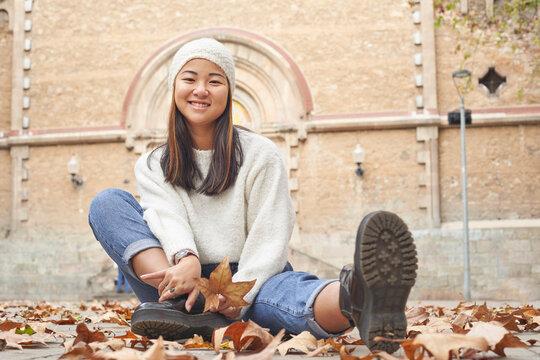 Smiling woman sitting by fallen dry leaf on footpath