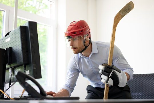 Businessman dressed up as ice hockey player working at desk in office