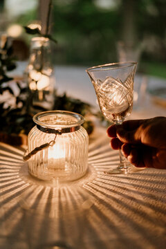 Hand of person holding wineglass in front of burning candle covered with glass bowl