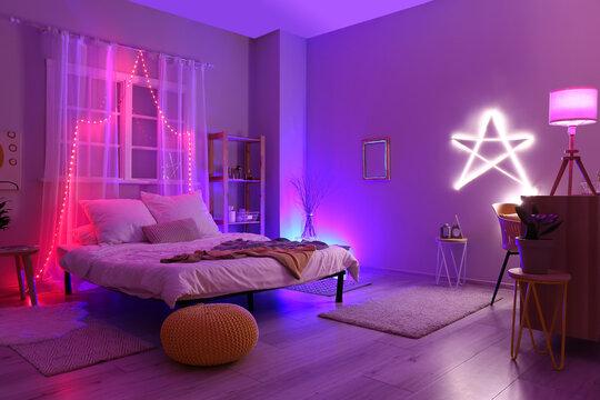 Interior of stylish bedroom with neon lighting