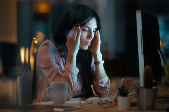 Young woman sitting at desk in office having headache