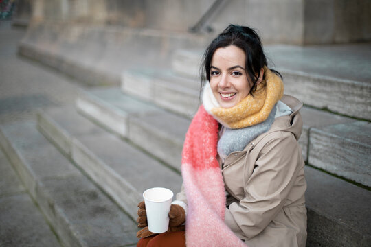 Smiling woman having coffee while sitting on steps during winter