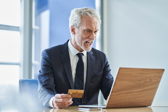 Successful businessman holding credit card and using laptop at desk in office