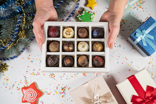 Handmade chocolate truffle candies in a white box on a christmas background. Directly above top view.
