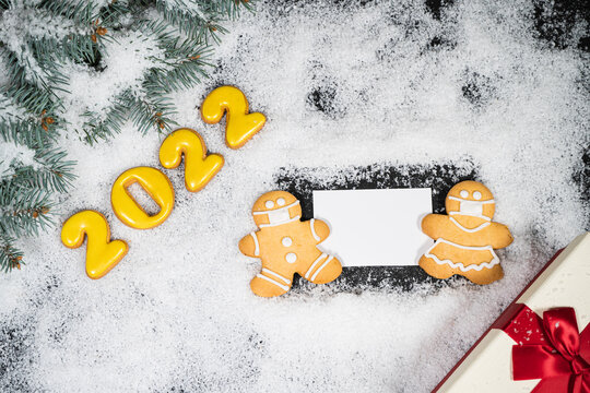 Christmas background with gingerbread on winter snow. Holiday mood card. Top view, copy space. Family traditions, DIY, celebration concept. Festive background with homemade gingerbread cookies.