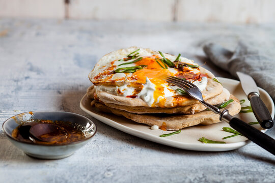 Flat bread with garlic yogurt, fried egg and chilli butter on chopping board