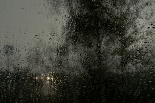 Night view from the inside through the windshield of a car with water droplets and headlights of an oncoming car