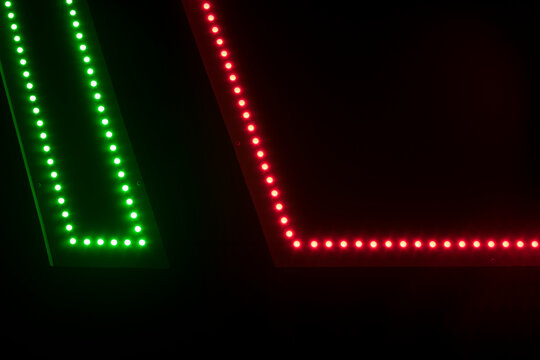 Dark background Detail of a neon sign made of green and red LEDs with copyspace
