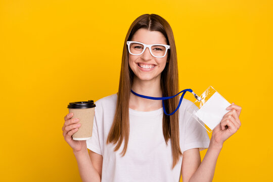 Photo of cheerful young happy positive woman good mood hold coffee name tag isolated on yellow color background