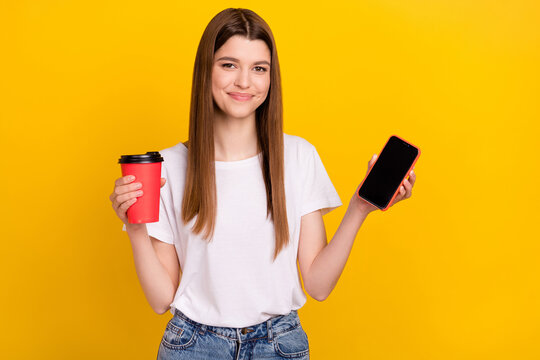 Photo of positive young happy woman smile show phone screen empty space hold coffee isolated on yellow color background