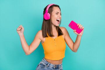 Fototapeta Photo of joyful crazy trendy stylish woman hold hands phone singer listen music isolated on teal color background obraz